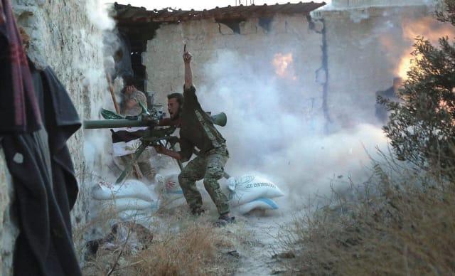 Un luchador rebelde hace un gesto mientras dispara su arma durante los enfrentamientos con las fuerzas leales al presidente de Siria, Bashar al-Assad, en la primera línea del barrio de Sheikh Saeed de Alepo, 23 de mayo de 2015 - REUTERS / Hosam Katan