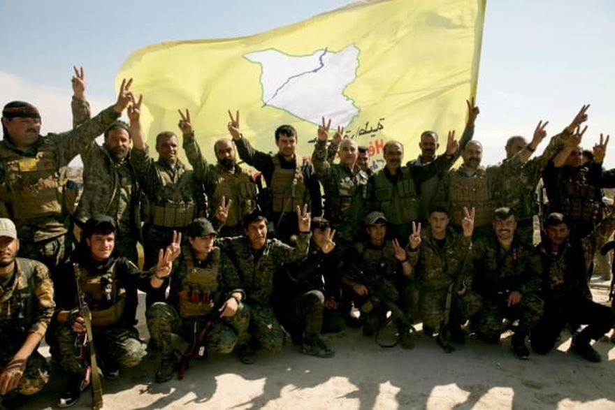 Los combatientes de las Fuerzas Democráticas Sirias respaldados por Estados Unidos posan para una foto en un tejado después de declarar el área libre de militantes del Estado Islámico, Baghouz, Siria, 23 de marzo de 2019. Crédito: Maya Alleruzzo, AP