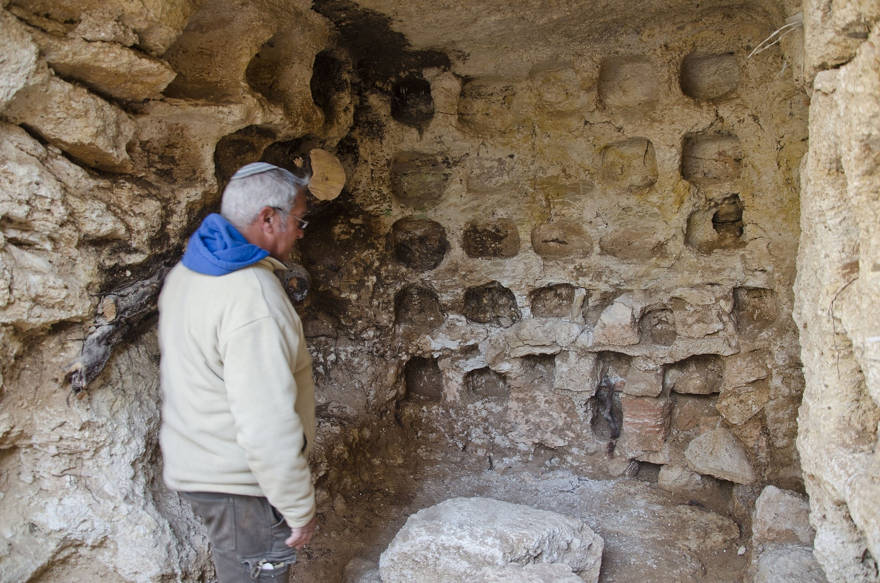 El arqueólogo Ya'akov Billig se encuentra cerca de un palomar ubicado en el sitio de entierro de la era Hasmonea que se está excavando en el barrio de Sharafat en Jerusalem. (Yoli Schwartz / Autoridad de Antigüedades de Israel)