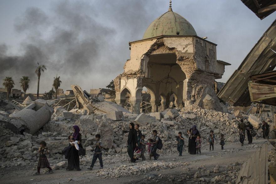 Los civiles iraquíes que huyen pasan por la mezquita al-Nuri destruida mientras las fuerzas iraquíes continúan su avance contra los militantes del Estado Islámico en la Ciudad Vieja de Mosul, Irak, el martes 4 de julio de 2017. (Foto AP / Felipe Dana)