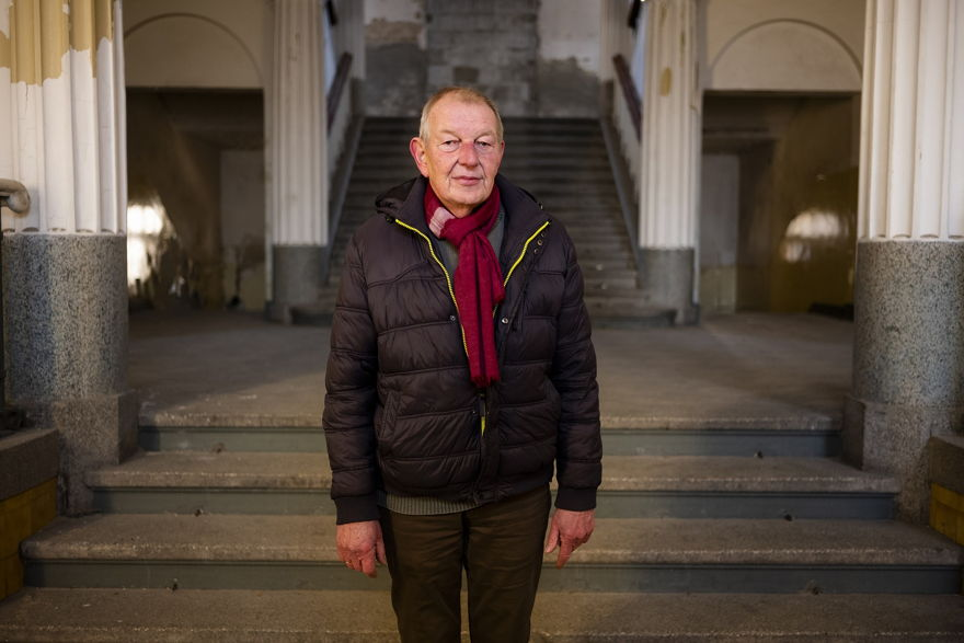 """El 22 de febrero de 2019, el guía Werner Borchert posa para una fotografía en la entrada principal de la abandonada """"Haus der Offiziere"""", la sede del alto mando militar de los soviéticos en la antigua Alemania Oriental en el barrio de Wuensdorf en Zossen. Unos 40 kilómetros (25 millas) al sur de Berlín. (AP / Markus Schreiber)"""