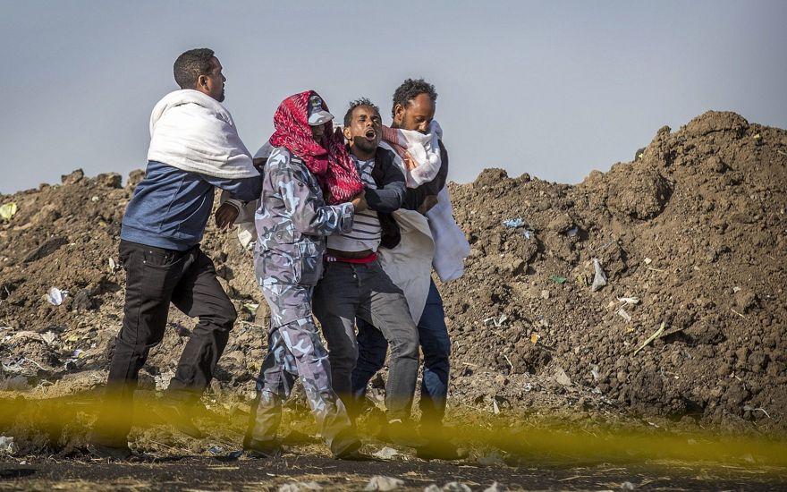 Un familiar afligido que perdió a su esposa en el accidente recibe ayuda de un miembro de las fuerzas de seguridad y otros en el lugar del accidente del Boeing 737 de Ethiopian Airlines, 8 de marzo de 2019. (AP / Mulugeta Ayene)
