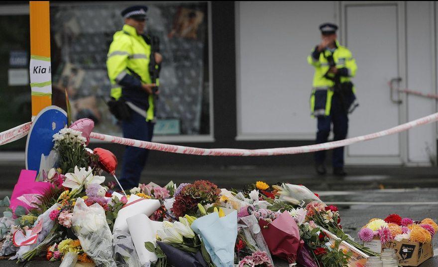 Flor descansa en un bloque de carretera, mientras dos agentes de policía montan guardia cerca del monumento improvisado cerca de la mezquita Linwood en Christchurch, Nueva Zelanda, sábado 16 de marzo de 2019. (AP / Vincent Thian)