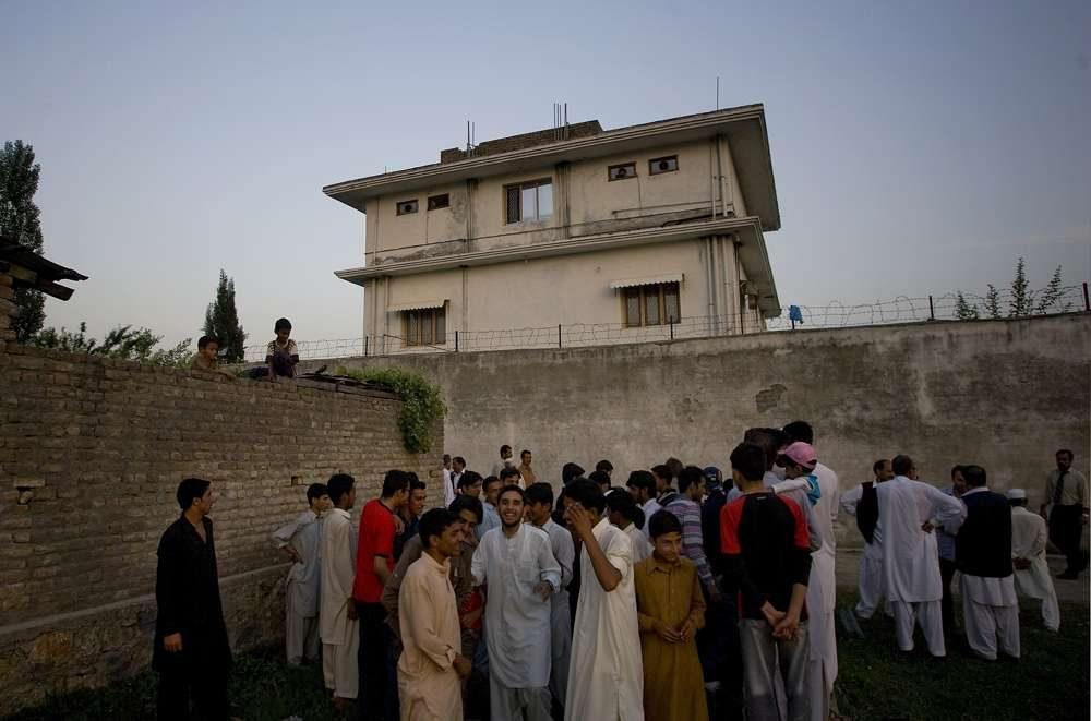 En esta foto de archivo del 3 de mayo de 2011, los residentes locales se reúnen fuera de una casa donde el líder de al-Qaeda, Osama bin Laden, fue asesinado en Abbottabad, Pakistán.(Foto AP / BKBangash, Archivo)