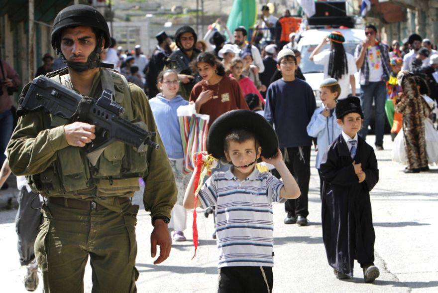 Los soldados de las FDI protegen a los celebrantes de Purim en la ciudad de Hebrón el jueves. (Crédito de la foto: Miriam Alster / Flash90)