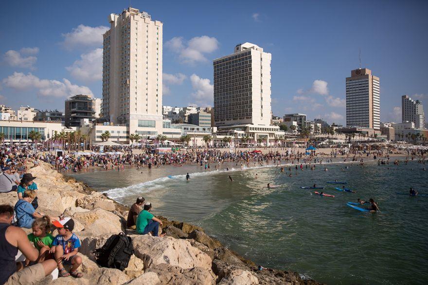 Los israelíes disfrutan del clima cálido en la playa de Tel Aviv, 27 de agosto de 2018. (Miriam Alster / FLASH90)