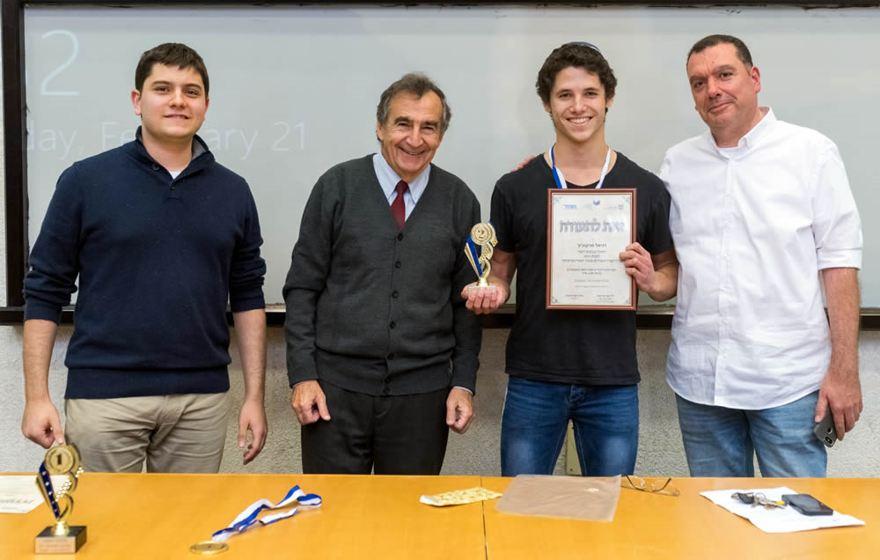 Daniel Markovitz de Netanya, flanqueado por el director de la Olimpiada Evgeny Frishman a su izquierda y el instructor Yitzhak Gvili a su derecha. Crédito: JCT.