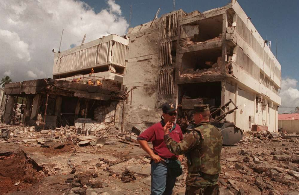 En esta foto de archivo del 15 de agosto de 1998, un infante de marina de los Estados Unidos conversa con un investigador del FBI frente a la embajada estadounidense dañada en la capital, Dar es Salaam, Tanzania, después de un ataque llevado a cabo por al-Qaeda.(Foto AP / Brennan Linsley, Archivo)