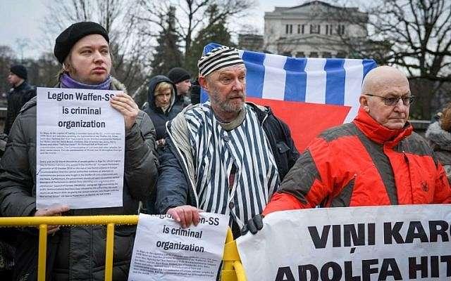 Los manifestantes sostienen carteles mientras organizan una contramanifestación contra los veteranos de la Legión letona, una fuerza que fue comandada por los alemanes nazis Waffen SS durante la Segunda Guerra Mundial, y sus simpatizantes desfilando hacia el Monumento a la Libertad en Riga, Letonia, el 16 de marzo de 2019. ( Ilmars ZNOTINS / AFP)