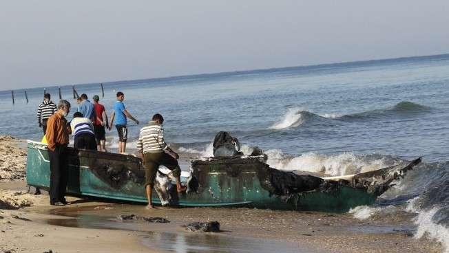 Pescadores árabes inspeccionan su barco pesquero destruido que fue arrastrado hacia la costa, cerca de la ciudad de Rafah, en el sur de la Franja de Gaza, el 26 de marzo de 2014. (Crédito de la foto: Said Khatib / AFP)
