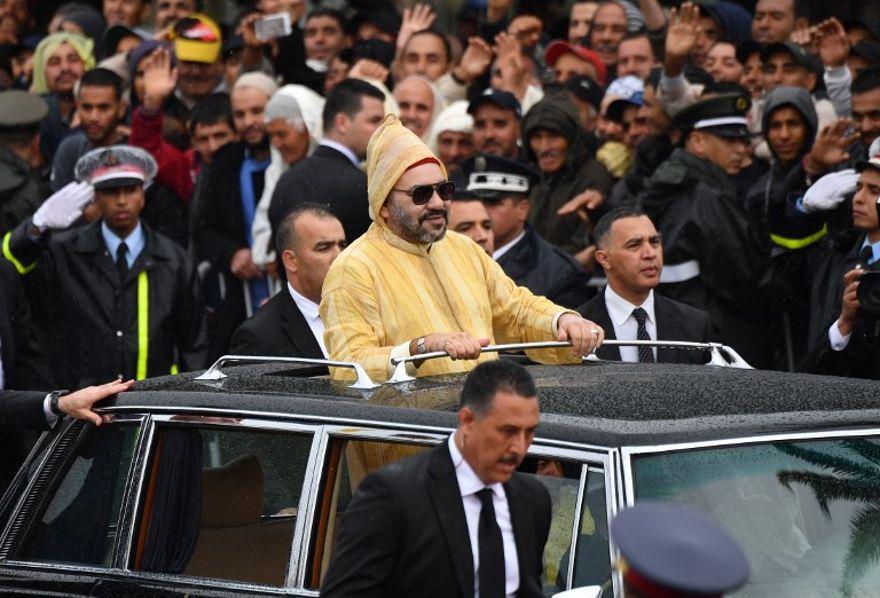 El rey Mohammed VI (R) sonríe a la multitud durante una ceremonia de bienvenida para el Papa Francisco en el centro de Rabat tras la llegada del Papa al país norteafricano el 30 de marzo de 2019. (Alberto PIZZOLI / AFP)