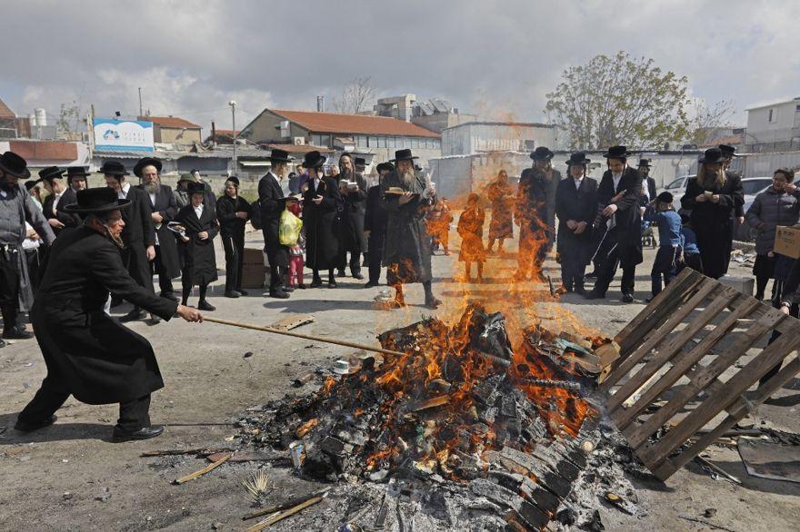 Los hombres judíos ultraortodoxos queman elementos fermentados durante el ritual de Biur Jametz el 19 de abril de 2019 en Jerusalem. (Menahem Kahana / AFP)