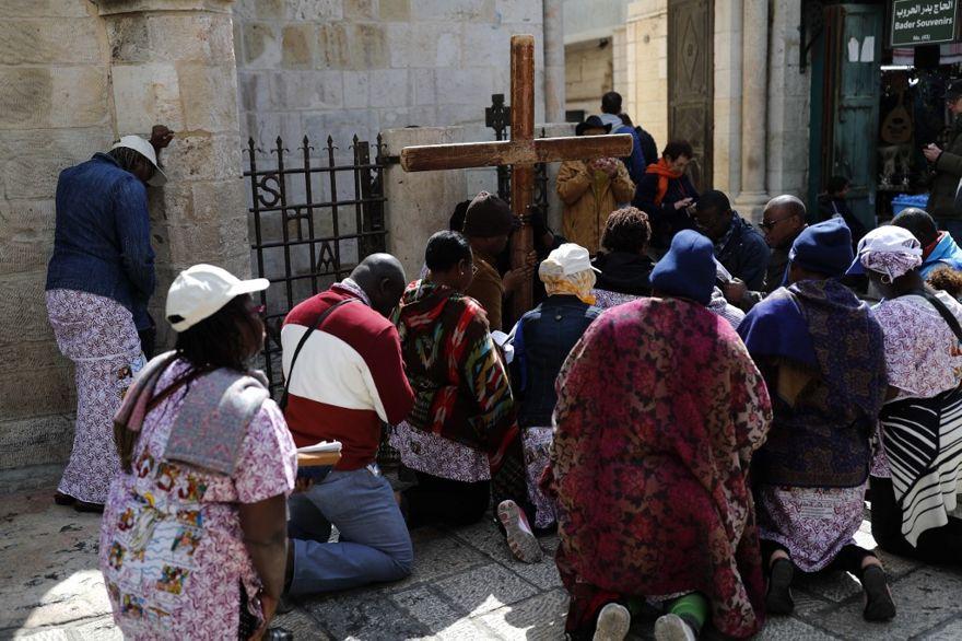 Los fieles se arrodillan para orar frente a una cruz de madera a lo largo de la Vía Dolorosa en la Ciudad Vieja de Jerusalem durante la procesión del Viernes Santo el 19 de abril de 2019. (Thomas Coex / AFP)