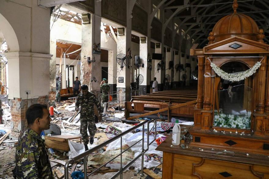 El personal de seguridad de Sri Lanka pasa junto a cadáveres cubiertos con mantas en medio de una explosión en el Santuario de San Antonio después de una explosión en la iglesia de Colombo el 21 de abril de 2019. (ISHARA S. KODIKARA / AFP)
