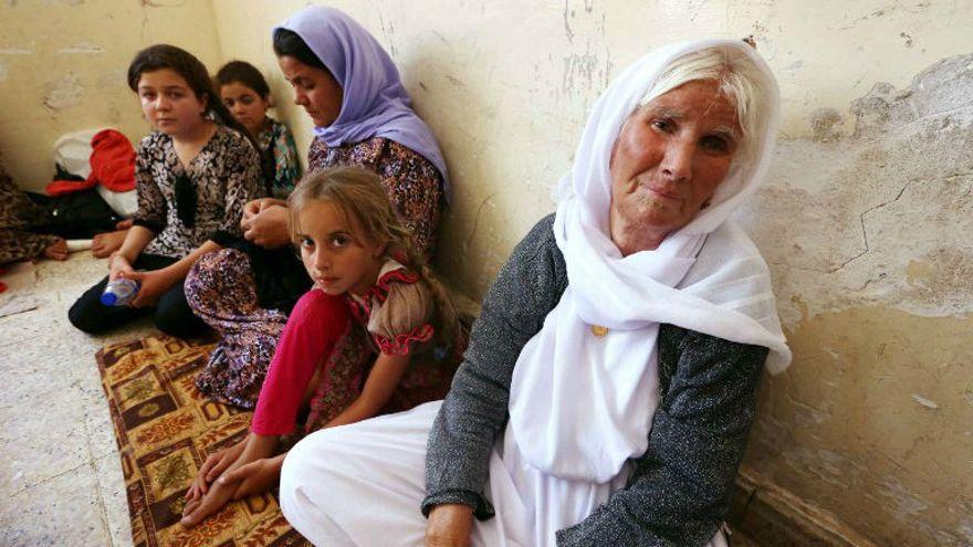Una familia yazidi iraquí que huyó de la violencia en la ciudad de Sinjar, en el norte de Irak, se sienta en una escuela donde se refugian en la ciudad kurda de Dohuk, en la región autónoma del Kurdistán de Irak, el 5 de agosto de 2014. (Crédito de la foto: AFP / Safin Hamed)