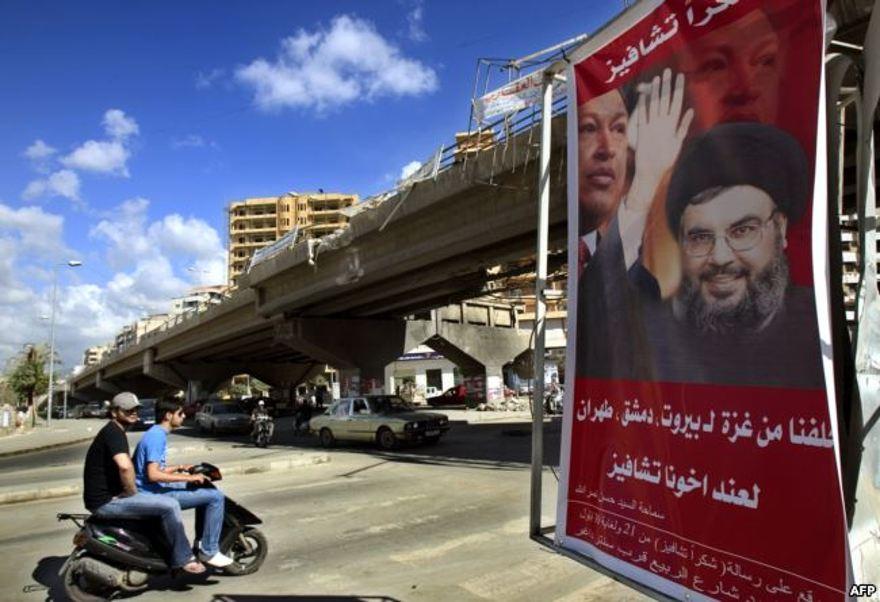 """ARCHIVO - Un póster muestra a Hassan Nasrallah, el secretario general de Hezbolá, y al presidente de Venezuela, Hugo Chávez, junto con un eslogan que dice """"Gracias Chávez"""" se ve colgado de un puente destruido en la entrada del suburbio sur de Beirut, el 21 de septiembre. , 2006."""