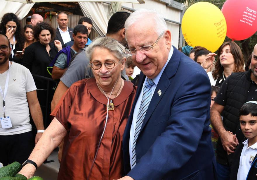 El presidente Rivlin y su esposa Nechama saludan a los israelíes en su Jerusalén Sukka. (Crédito de la foto: Mark Neiman / GPO)