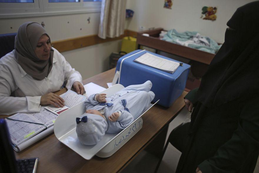 En esta foto del 14 de enero de 2018, una mujer palestina hace controlar a su hijo en una clínica administrada por la UNRWA en el campamento de refugiados de Shati, ciudad de Gaza. (Foto AP / Khalil Hamra)