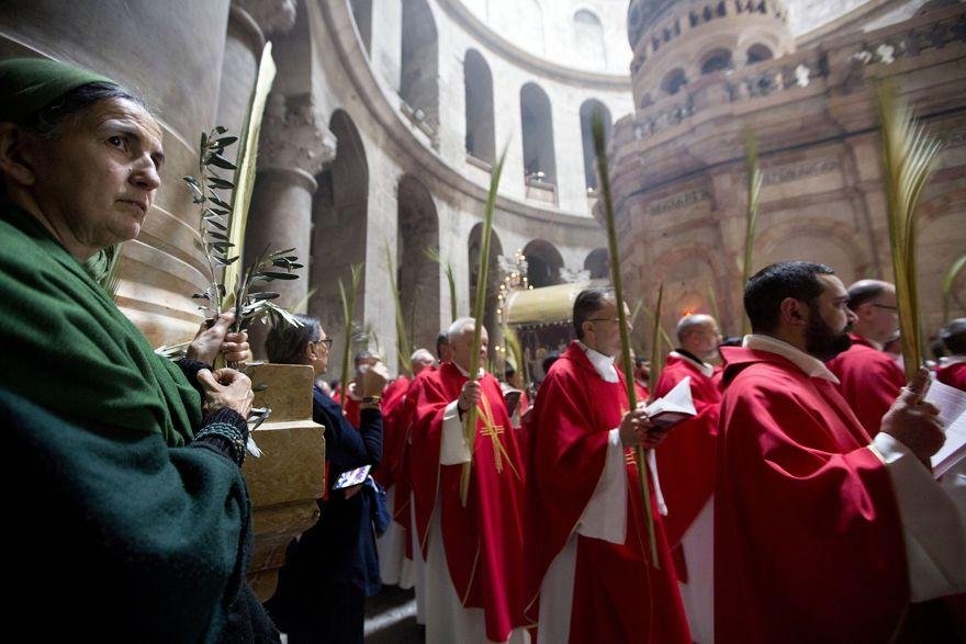 Los sacerdotes católicos llevan hojas de palma en la Iglesia del Santo Sepulcro, tradicionalmente muchos cristianos creían que era el lugar de la crucifixión y el entierro de Jesús en la Ciudad Vieja de Jerusalem, el 14 de abril de 2019. (AP Photo / Sebastian Scheiner)