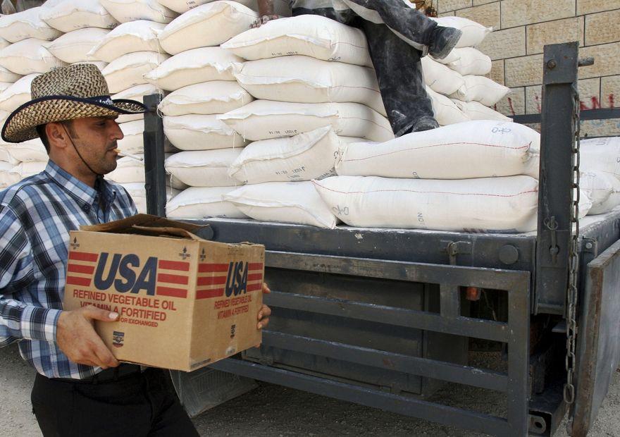 Un palestino lleva una caja de aceite vegetal mientras camina sobre bolsas de harina en un camión donado por USAID, o la Agencia de los Estados Unidos para el Desarrollo Internacional, en un depósito en la aldea de Anin, cerca de Jenin, 4 de junio de 2008 (AP Foto / Mohammed Ballas)