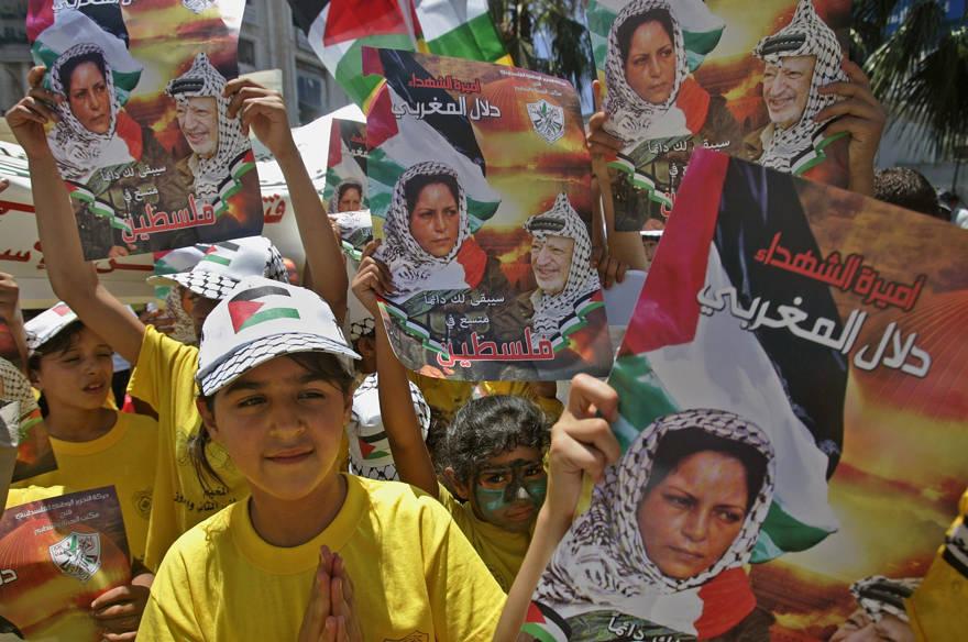 Las niñas palestinas sostienen carteles que muestran a Dalal Mughrabi en la ciudad de Ramallah, el 16 de julio de 2008. El cuerpo de Mughrabi fue uno de los 199 cuerpos transferidos al Líbano como parte del intercambio de prisioneros. (Foto AP / Muhammed Muheisen)