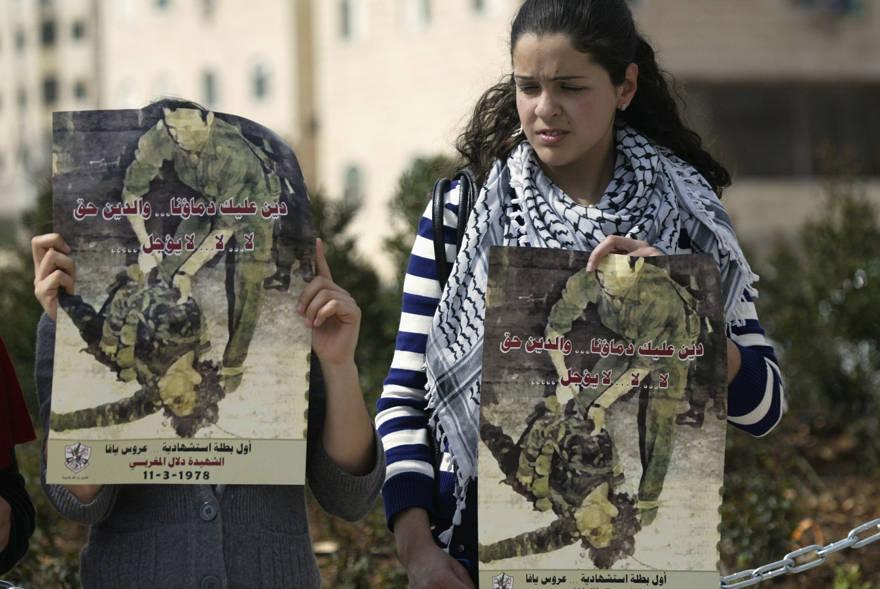 """En esta foto tomada el 11 de marzo de 2010, los palestinos sostienen carteles con una foto del terrorista palestino Dalal Mughrabi durante una protesta en la ciudad de Ramallah.. El texto de la pancarta dice en árabe: """"Le debemos nuestra sangre y la deuda es un derecho que no se puede posponer"""". (Foto AP / Majdi Mohammed)"""