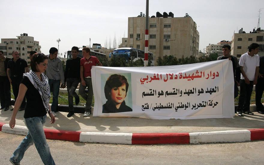 En esta fotografía del 11 de marzo de 2010, los palestinos sostienen una pancarta con una foto de Dalal Mughrabi, una terrorista palestina que mató a decenas de civiles israelíes en un secuestro de un autobús en 1978 en Israel, visto en retratos, mientras protestaban en la ciudad de Ramallah. (Foto AP / Majdi Mohammed)