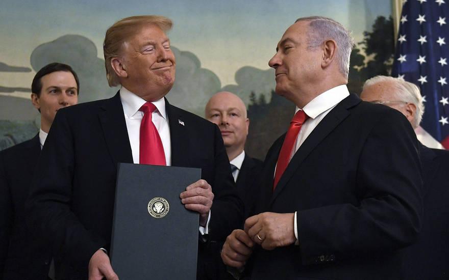 El presidente de los Estados Unidos, Donald Trump, sonríe al primer ministro israelí, Benjamin Netanyahu, a la derecha, después de firmar una proclamación que reconoce formalmente la soberanía de Israel sobre los Altos del Golán, en la sala de recepción diplomática de la Casa Blanca en Washington, el lunes 25 de marzo de 2019 (Foto AP / Susan Walsh)