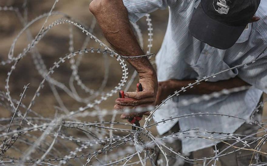 Ilustrativo. Un hombre palestino usa cortadores de alambre en una cerca de alambre de púas a lo largo de la frontera de Gaza con Israel el, 4 de mayo de 2018. (Wissam Nassar / Flash90 / File)