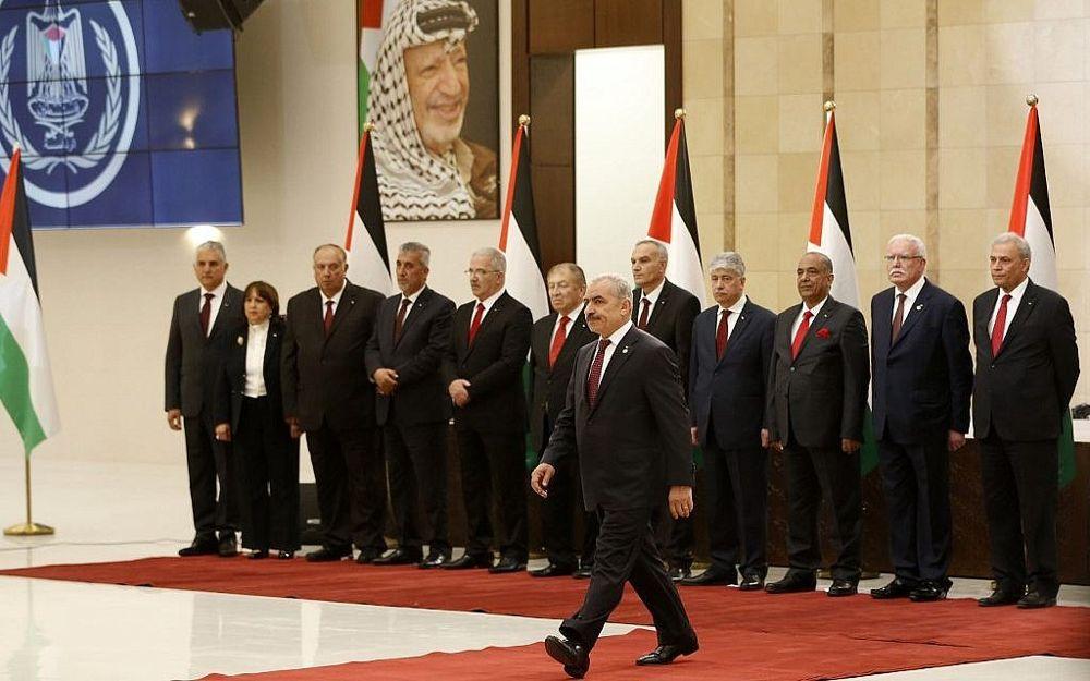 El primer ministro de la Autoridad Palestina entrante, Mohammad Shtayyeh, camina hacia el podio para pronunciar un discurso en la ciudad cisjordana de Ramallah, el 13 de abril de 2019. (Abbas Momani / AFP)