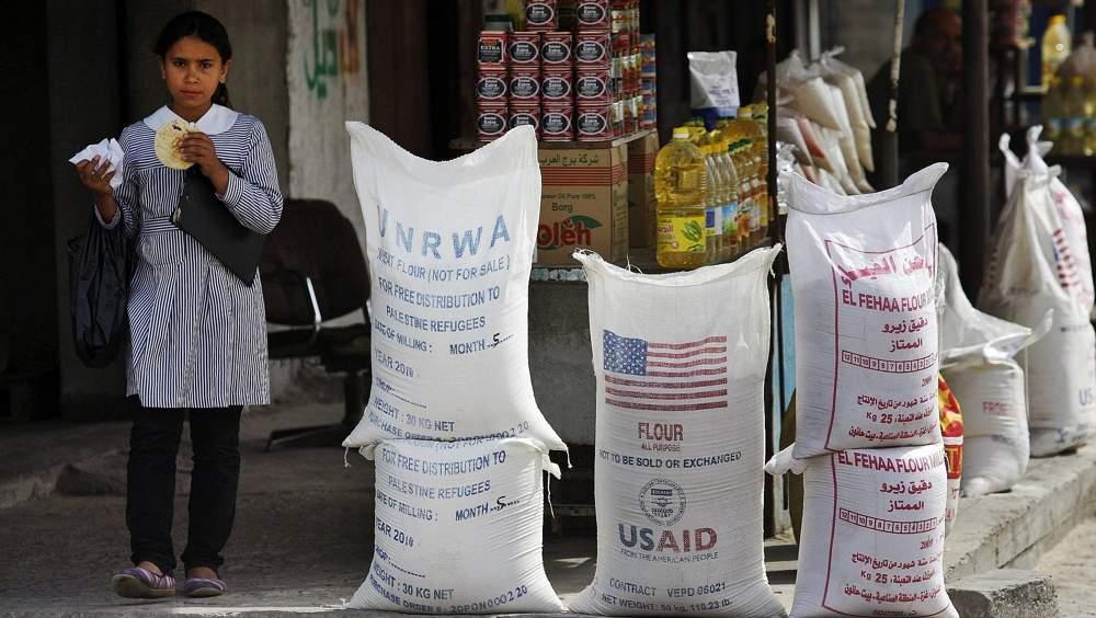 Una alumna árabe pasa por delante del Organismo de Obras Públicas y Socorro de las Naciones Unidas (UNRWA), y USAID, ayuda humanitaria el 6 de junio de 2010 en el campo de refugiados de Shatie, en la ciudad de Gaza. (Foto AP / Lefteris Pitarakis, Archivo)