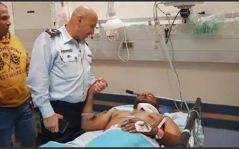 El comisionado adjunto de prisiones Asher Vaknin (izquierda) visita al guardia de la cárcel Sagi Silwan, quien fue apuñalado en el cuello por un prisionero de Hamas en la prisión de Ketziot el 24 de marzo de 2019. (Captura de pantalla de la Autoridad de Prisiones de Israel)
