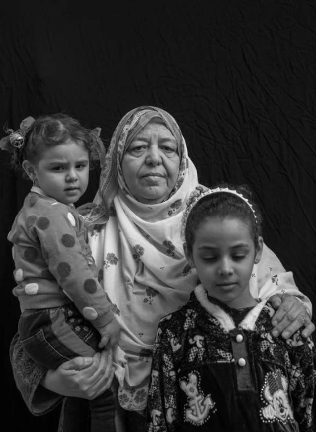 """Hawla Mahdi Salah, de 67 años, posa para un retrato con sus nietas Safae Khalid Adnan, de 2, y Hawla Khalid Adnan, de 9, en Mosul, Irak. El 26 de junio de 2017, un ataque aéreo destruyó su hogar mientras estaban dentro. Salah perdió a nueve miembros de la familia en la explosión, incluidos dos hijos y tres nietos, dejándola a cargo de Safae y Hawla, que quedaron huérfanos, junto con otros seis nietos. """"Solo Alá sabe si la Ciudad Vieja será reconstruida"""", dice ella. - Victor J. Blue"""