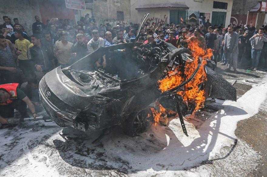 El personal de emergencia palestino intenta apagar el fuego en un automóvil perteneciente al miembro principal del grupo terrorista Hamas, Hamed Hamdan al-Khodari, luego de que fue golpeado por un ataque aéreo israelí en la ciudad de Gaza el 5 de mayo de 2019. (MAHMUD HAMS / AFP)