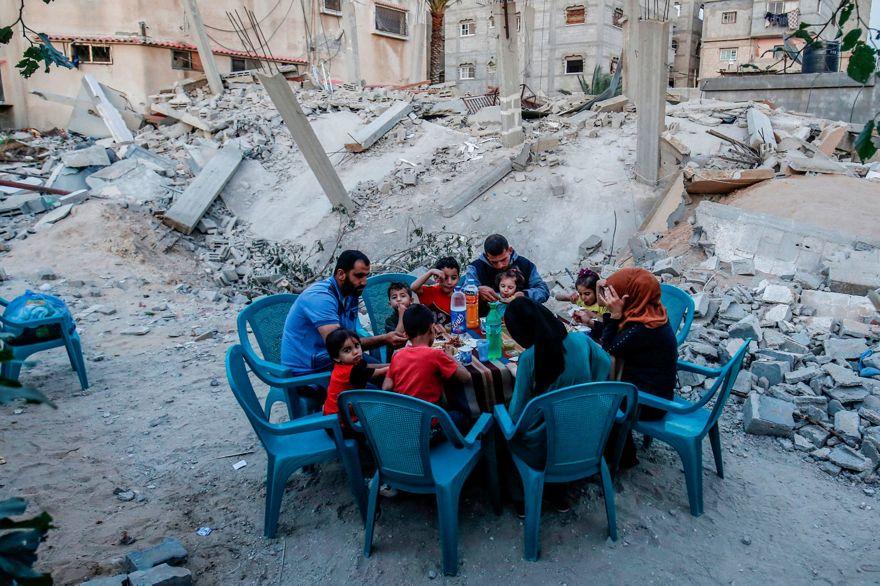 Familia palestina rompe el ayuno junto a su casa que fue destruida durante la escalada de dos días, Rafah, Franja de Gaza, 8 de mayo de 2019.  - AFP