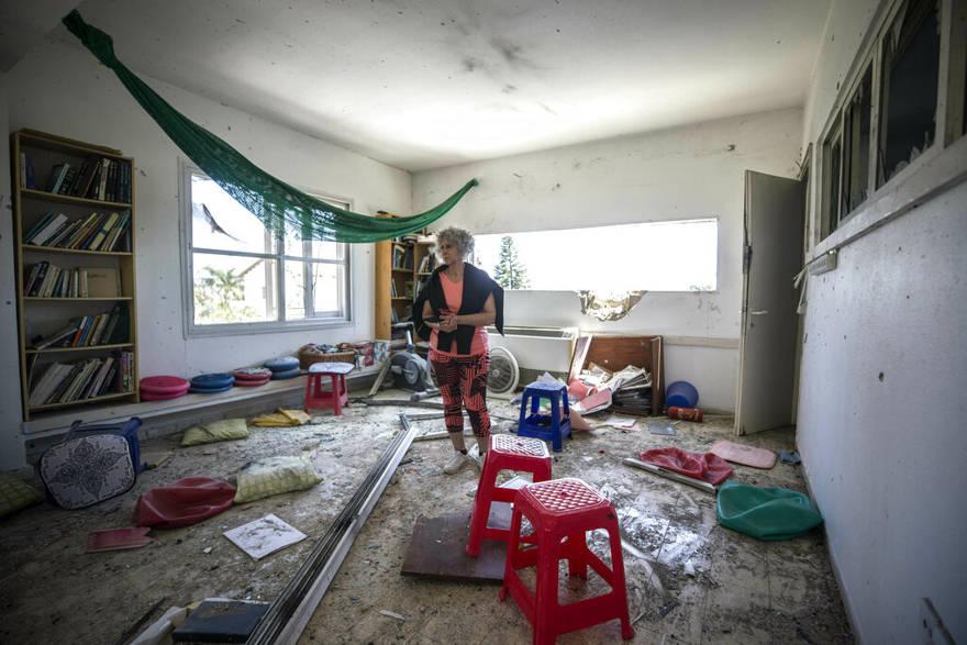 Una mujer observa el daño causado por un cohete lanzado desde Gaza que golpeó una casa en un moshav en Israel, cerca de la frontera con Gaza, el sábado 4 de mayo de 2019. (AP Photo / Tsafrir Abayov)