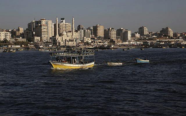 Los barcos pesqueros palestinos navegan hacia las aguas del mar Mediterráneo en la ciudad de Gaza, el lunes 9 de julio de 2018, con los edificios de la ciudad de Gaza vistos como fondo. (Foto AP / Adel Hana)