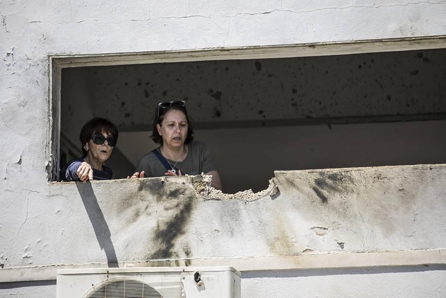 Las mujeres observan el daño causado por un cohete disparado desde Gaza que golpeó una casa en el sur de Israel cerca de la frontera con Gaza, sábado 4 de mayo de 2019 (AP Photo / Tsafrir Abayov)
