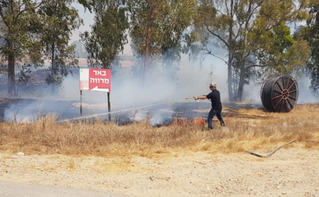 Un bombero lucha contra uno de los incendios en el Negev occidental por globos incendiarios de la Franja de Gaza | Fotografía: Moshe Bruchi / JNF