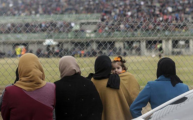 Mujeres palestinas miran el partido de fútbol entre Al-Nuseirat y Al-Jalaa, de pie frente a la valla del estadio en el campamento de refugiados de Nuseirat, al sur de la ciudad de Gaza, el 28 de enero de 2018. (AFP PHOTO / MAHMUD JAMS)