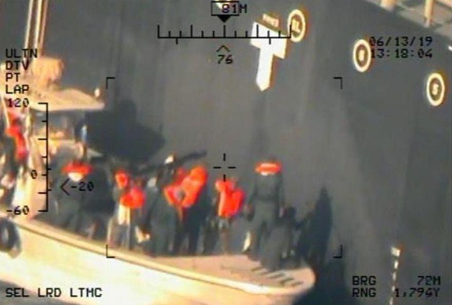 Esta imagen, publicada por el Departamento de Defensa de los EE. UU. El lunes 17 de junio de 2019 y tomada de un helicóptero de la Armada de los EE. UU., Muestra lo que la Armada dice que son miembros del Cuerpo de la Guardia Revolucionaria Islámica, que están retirando una mina de laca sin explotar del M / T Kokuka. Valiente. (Departamento de Defensa de los Estados Unidos a través de AP)