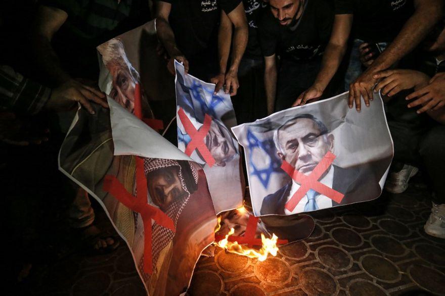 Los palestinos queman carteles del presidente de Estados Unidos, Donald Trump, el primer ministro Benjamin Netanyahu y el rey Hamad al-Khalifa de Bahrein, en la ciudad de Rafah, al sur de la Franja de Gaza, el 25 de junio de 2019, durante una protesta contra la conferencia de Paz a la Prosperidad dirigida por Estados Unidos en Bahrein. (Dijo KHATIB / AFP)