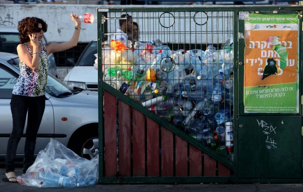 Una mujer tira una botella al contenedor de reciclaje en el centro de Jerusalem. (Crédito de la foto: Nati Shohat / Flash90)