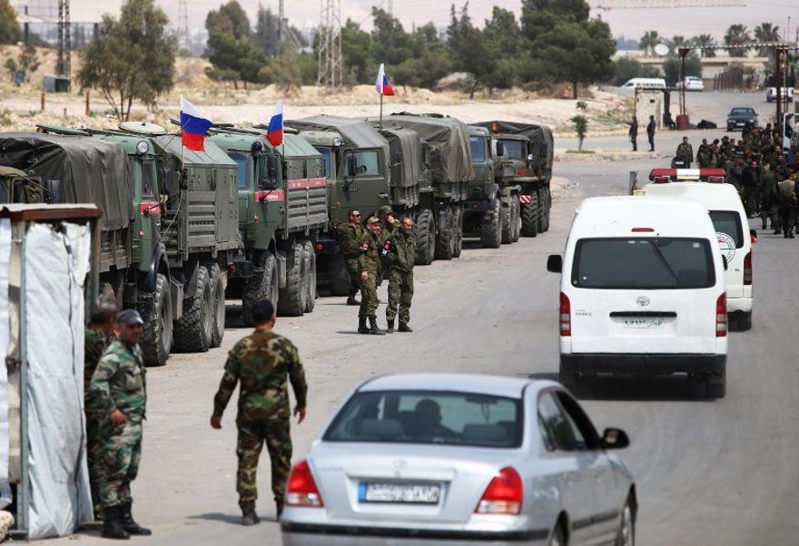 Soldados sirios y rusos en la entrada del campo de Wafideen en Siria, el 12 de abril de 2018. (Foto de AFP / Youssef Karwashan)