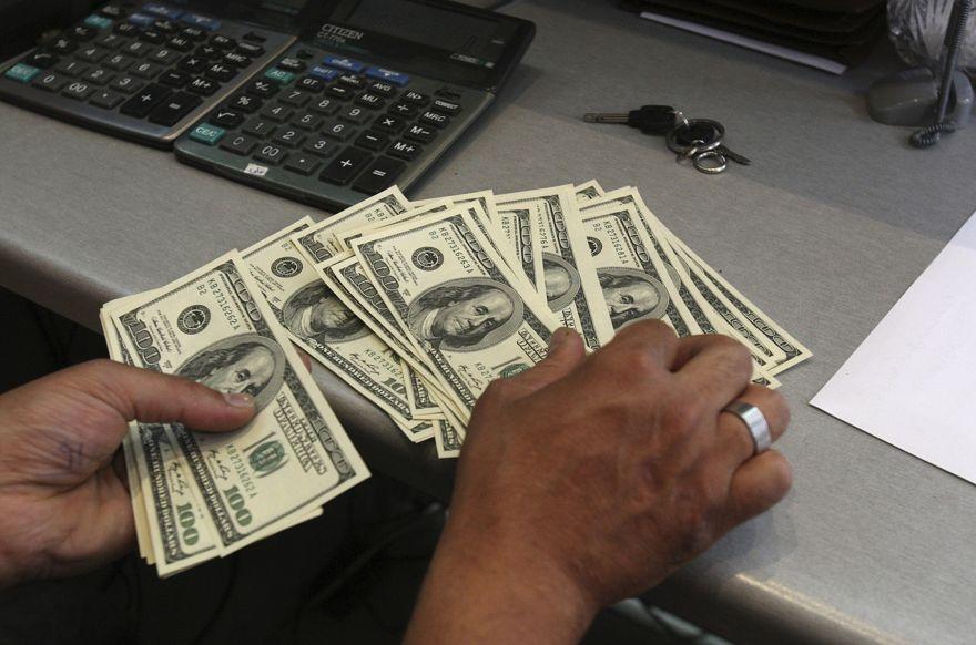 Un trabajador de la oficina de cambio de divisas, cuenta dólares estadounidenses, en el centro de Teherán, Irán, 9 de junio de 2011. (AP / Vahid Salemi)