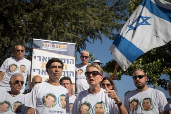 Los padres en duelo de Hadar Goldin y otros miembros de la familia y simpatizantes se reúnen fuera de la ceremonia conmemorativa estatal para la Operación Borde Protector en Mount Herzl el 23 de julio de 2019. (Noam Revkin Fenton / Flash90)