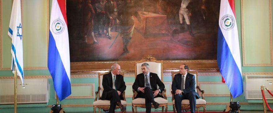 En esta imagen distribuida por la Oficina de Prensa del Gobierno de Paraguay, el presidente Mario Abdo Benítez, en el centro, habla con el nuevo embajador de Israel