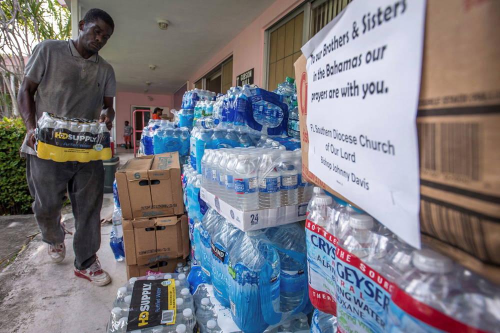 Un voluntario junta agua para los damnificados (EFE)