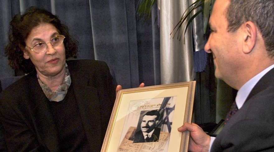 El primer ministro israelí, Ehud Barak, recibe una foto de un nuevo sello postal que conmemora a Eli Cohen, de su viuda Nadia Cohen, el 25 de enero de 2000. (Menahem Kahana / AFP / Getty Images)