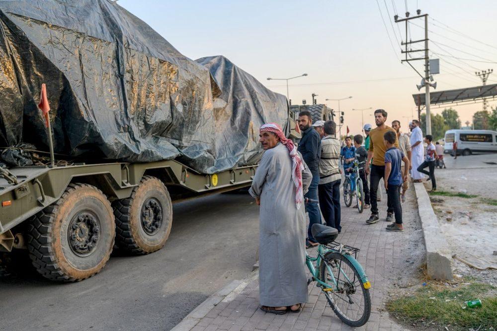 Los civiles turcos miran el convoy de un ejército turco que se dirige hacia la frontera siria cerca de Akcakale en la provincia de Sanliurfa el 9 de octubre de 2019 (BULENT KILIC / AFP)